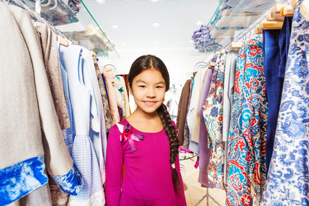 children clothing: Small girl with beautiful braid standing between clothes on the hangers in the shopping mall