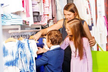 mujer hijos: Mujer con dos hijos juntos de compras en la tienda de ropa y de la elección de la prenda de vestir derecho