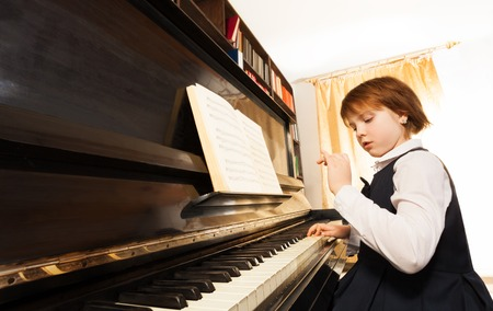 concentrated: Concentrated beautiful small girl in school uniform playing the piano with notes during lesson indoors