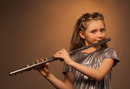 View of girl with long hair holding and playing on silver flute over gel colored dark background Standard-Bild