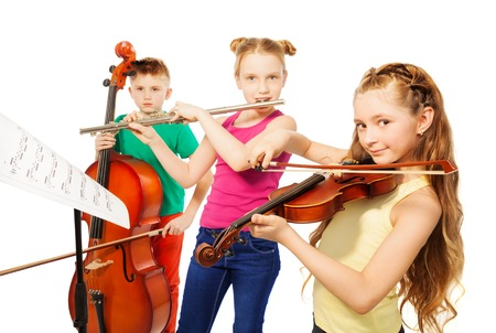 Two girls and boy playing on musical instruments together on white background