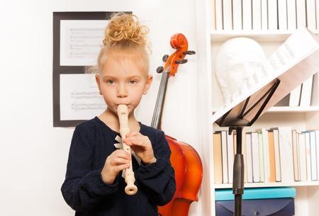 flauta: Chica rubia rizada toca la flauta de pie cerca del violonchelo en la escuela musical