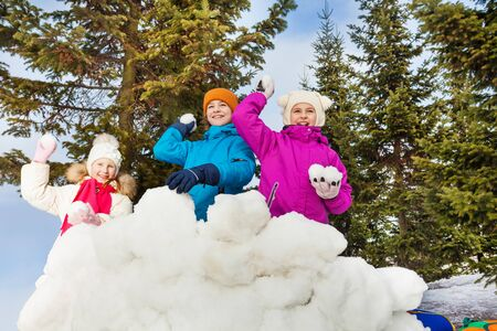 snowballs: Group of kids play snowballs game together standing behind the snow wall fortress with fir forest on the background during winter day