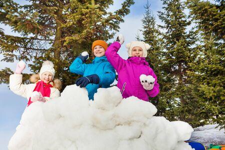 palle di neve: Gruppo di bambini che giocano gioco palle di neve insieme in piedi dietro la fortezza parete di neve con la foresta di abeti sullo sfondo durante la giornata invernale