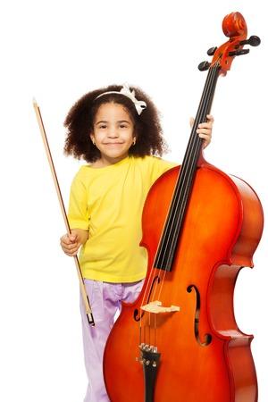 orquesta clasica: Niña africana que sostiene el violoncelo con fiddlestick listo para jugar de pie en el fondo blanco