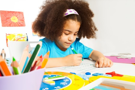 kids writing: Small African girl writing letters with pencil on the paper while sitting at the table indoors