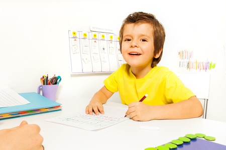 autistic: Smiling boy draws with pencil on the paper during Applied Behavior Analysis ABA sitting at the table indoors