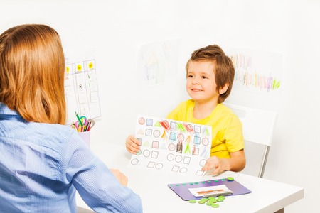 autistic: Happy boy holding the drawing with colored shapes with his parent sitting opposite at the table in the room