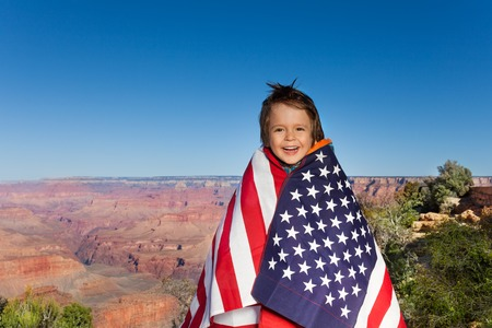 grand kids: Cheerful small boy who is bundled up into American flag with Grand Canyon National Park view, USA on 4th July