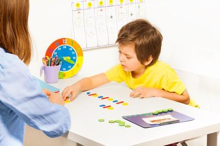 Geconcentreerde jongen die kleurrijke muntstukken in orde tijdens de ontwikkeling van spel met zijn moeder aan tafel zitten binnenshuis Stockfoto