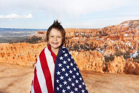 bundled: Cute laughing boy who is bundled up into American flag, Bryce Canyon National Park, USA Stock Photo