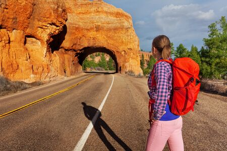 back roads: Close-up of girl with rucksack on the road near Red canyon during sunny summer day in USA