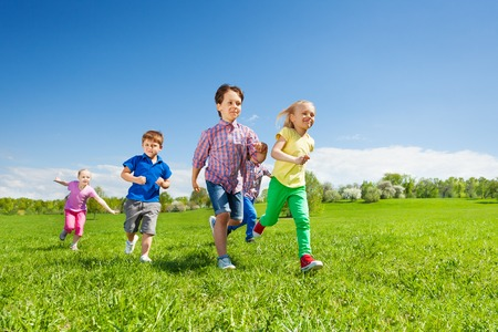 Happy group of children running in the green park during daytime and sunny beautiful weather