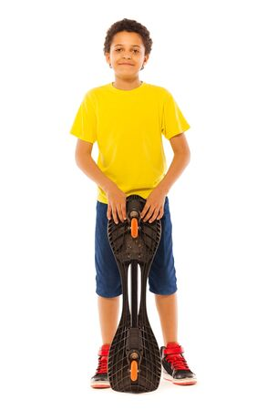 full height: Nice little African black boy standing with skate board in full height isolated on white