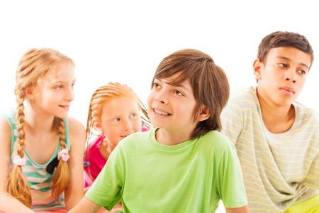 school age boy: Happy smiling little school age boy sitting with friends looking aside