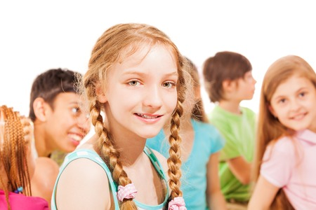 ponytails: Cute smiling school age girl with ponytails sit with group of her friends on background