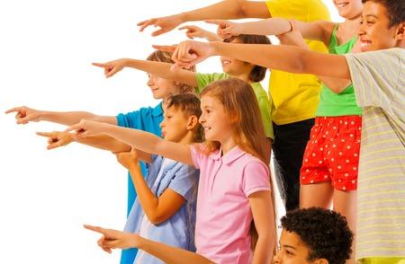 multitud gente: Gran grupo de niños los niños y niñas que apuntan vista lateral del dedo en el perfil aislado en blanco