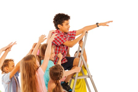 mates: African  boy climbing on the leader up with his mates trying to pull him down representing concept of school competitiveness