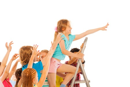 competitiveness: Caucasian girl climbing on the ladder up with his mates trying to pull him down representing concept of school competitiveness Stock Photo