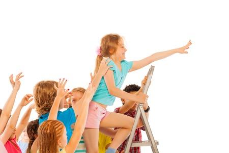 competitividad: Ni�a blanca subiendo en la escalera con sus compa�eros tratando de tirar de �l hacia abajo representa el concepto de la competitividad de la escuela