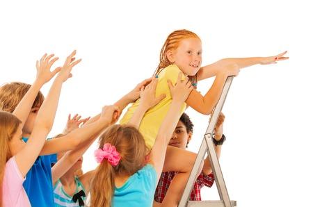 competitividad: Subida linda chica roja en la escalera con sus compa�eros tratando de tirar de �l hacia abajo representa el concepto de competitividad entre los compa�eros de la escuela Foto de archivo