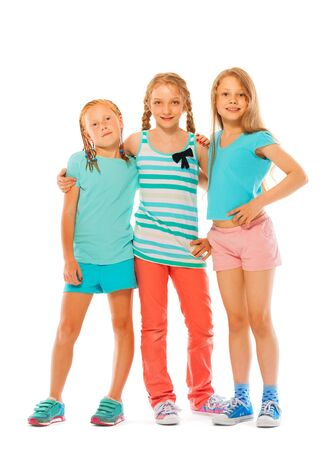 full height: Full height portrait of three happy girls standing together hugging isolated on white