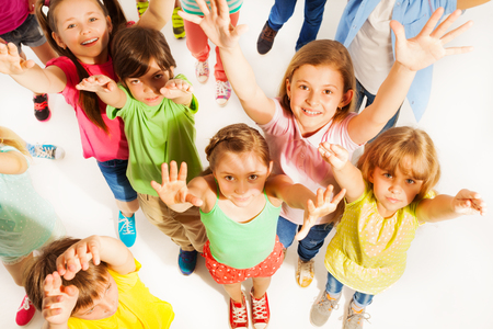 lifting hands: Close up of bunch of kids wearing colorful clothes and lifting hands in the air isolated on white