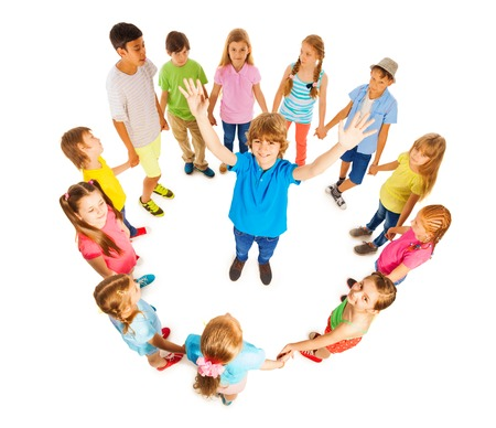 hands lifted up: Cute school age Caucasian boy with lifted up hands standing in the circle of diverse looking kids