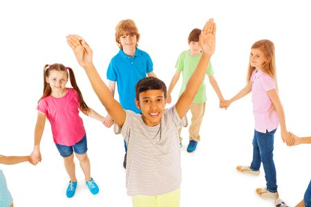 lifted hands: Handsome smiling boy with lifted hands stand in the circle of other kids isolated on white Stock Photo