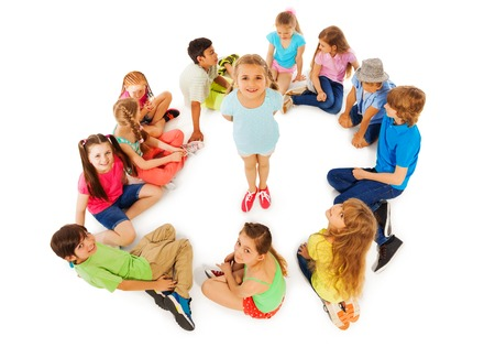 nice looking: Nice looking little girl stand in the center of circle of kids smile and look up