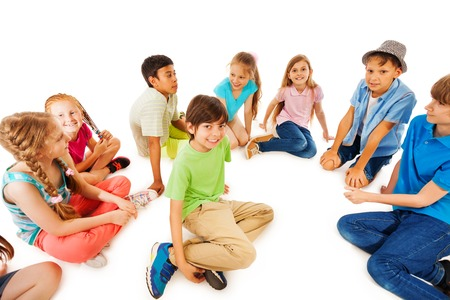 happy smiling: Group of kids sit in the circle with one boy in the center happy and smiling, isolated on white