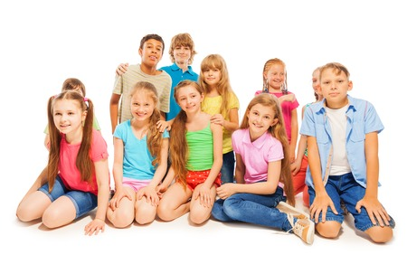 8 years old: Large bunch of 8 years old kids sitting on the floor smiling at camera isolated on white