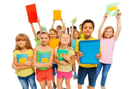 mucha gente: Felices los niños después de los exámenes sonriendo levantando los libros de texto