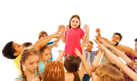 popularity: Girl is overwhelmed with popularity in class standing in the circle of kids pointing fingers at her Stock Photo