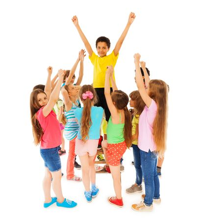 team leadership: Happy African ethnicity boy stands in circle of large group friends isolated on white with raised hands