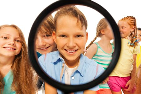 group search: Smiling happy face of the boy through the magnified glass with big smile and group of friends