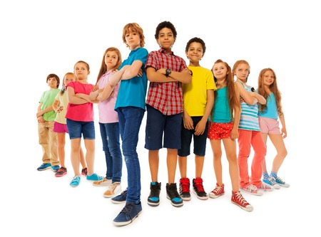 Group of dominate looking children boys and girls stand together with closed hands and look down confidently isolated on white