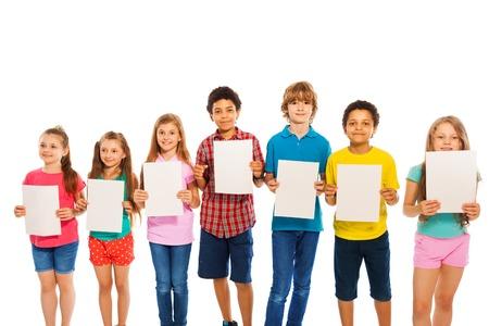 file d attente: Beaucoup de garçons et filles diverses enfants debout avec des feuilles de papier vierges isolé sur blanc Banque d'images