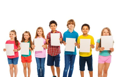 waiting in line: Many diverse boys and girls children standing with blank paper sheets isolated on white