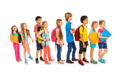 Many happy kids African and Caucasian standing in a line with backpacks and books Stock Photo