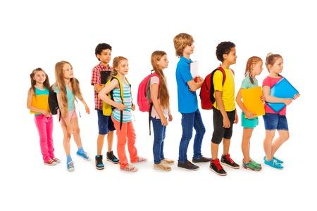 fila de personas: Muchos niños felices de pie africano y caucásico en una línea con mochilas y libros Foto de archivo
