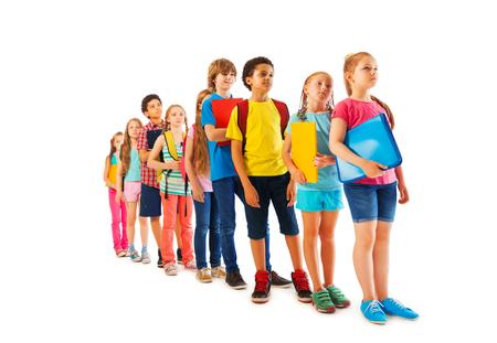 Vele gelukkige kinderen staan in een lijn met schoolboeken geïsoleerd op wit Stockfoto