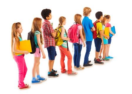 in the back: Volver la vista de la cola de ni�os y ni�as de diversos estudiantes de pie con libros y mochilas titulares