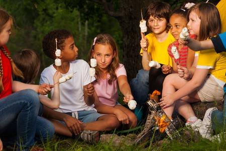 campamento: Grupo de niños con malvavisco cerca de hoguera en acampar en el bosque juntos en la noche