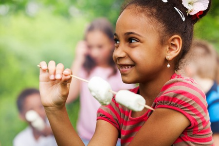 Portrait of African girl holding stick with marshmallow during camping in the forest with other kids