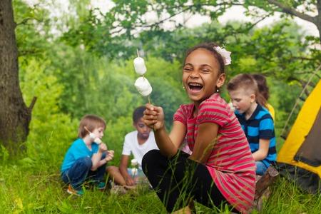 Lachend Afrikaans meisje houdt stok met marshmallow tijdens het kamperen in het bos met andere kinderen