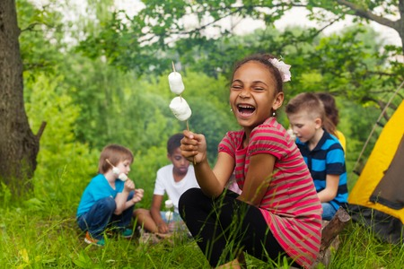 Laughing African girl holding stick with marshmallow during camping in the forest with other kids