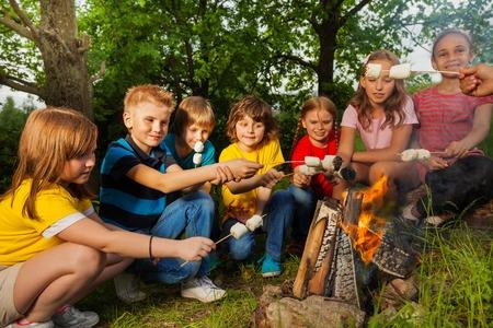 Glückliche Freunde, die in der Nähe von Lagerfeuer mit Marshmallow während Camping im Wald zusammen