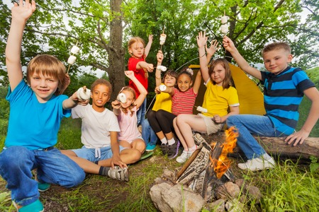 Teenagers with arms up near bonfire hold toasted marshmallow treats during camping in the forest together