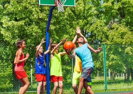 diverse: Group of happy teenagers playing basketball on playground during summer